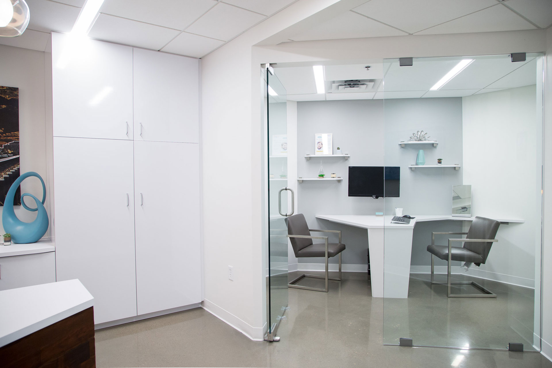 The dentist's office features high tech gadgets and a sleek, white interior design.