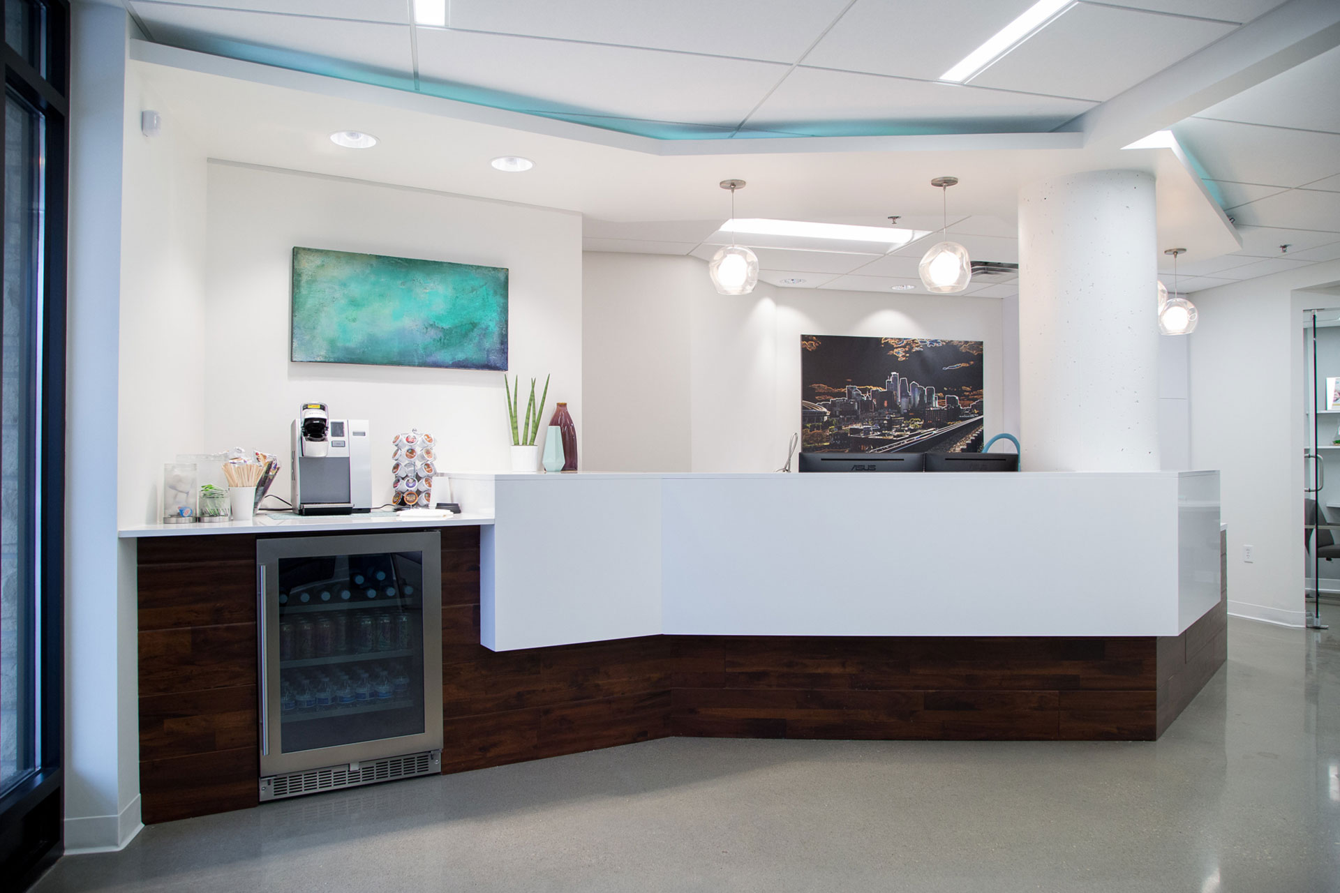 The dental office features snacks, water, and a coffee machine in the sleek, clean waiting area for patients.